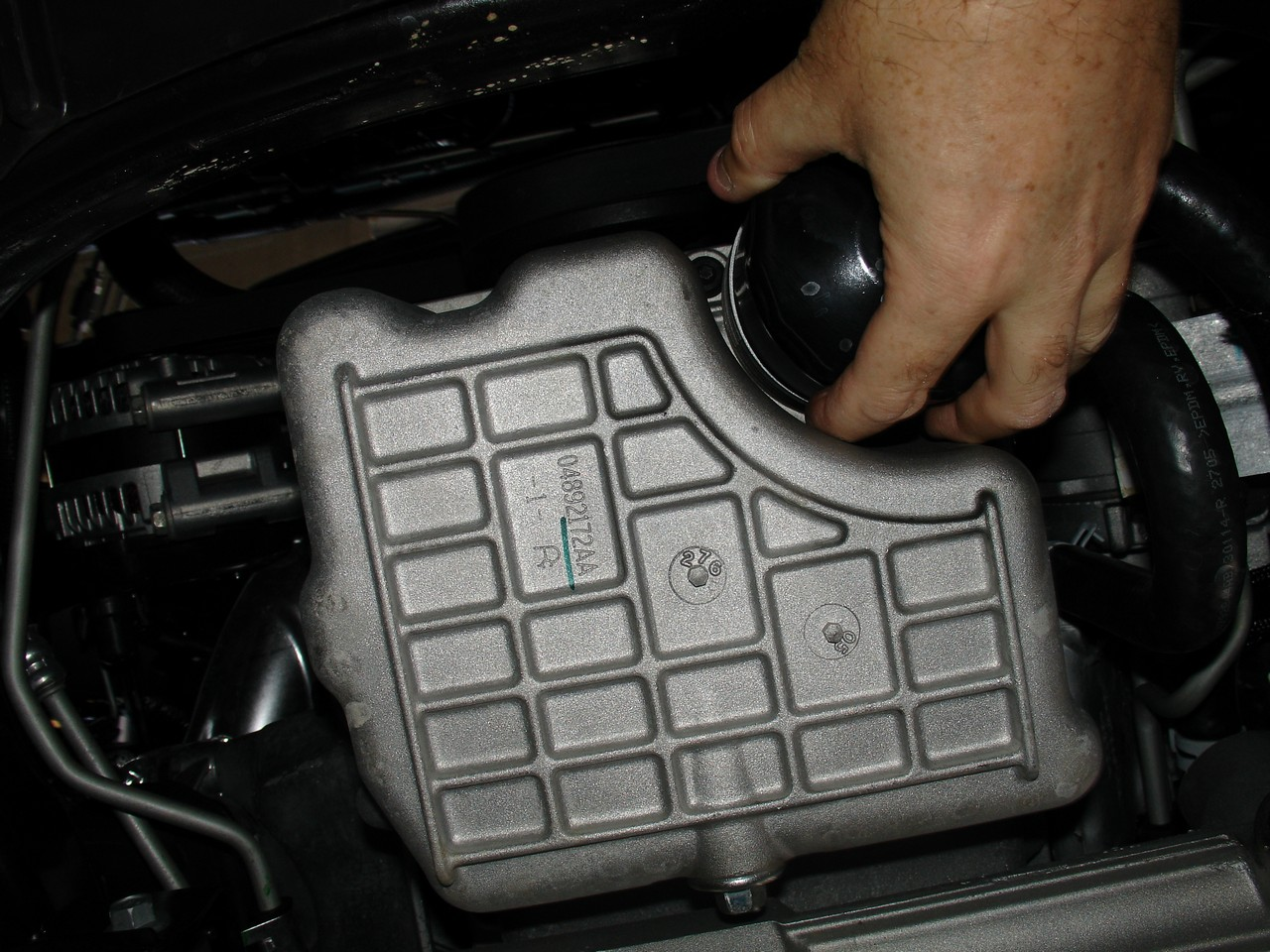 With the splash guard out of the way, you can see the oil pan and filter. I  try to get it off by hand, but it won't budge.